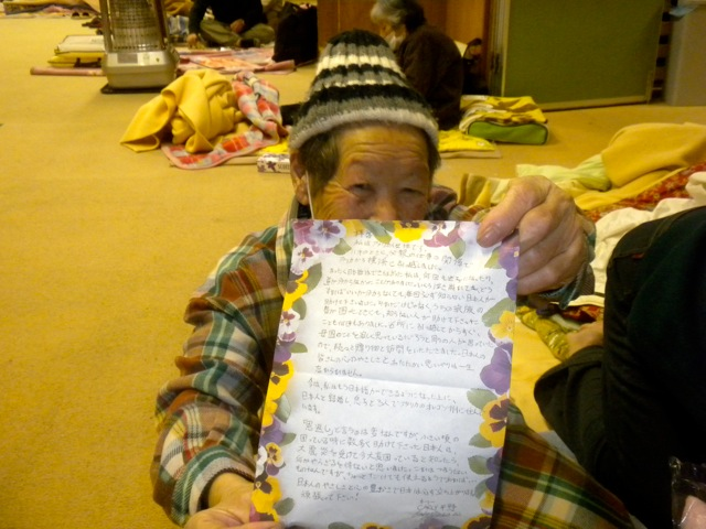 Photo of elderly woman at Otsu Port shelter loving her letter!