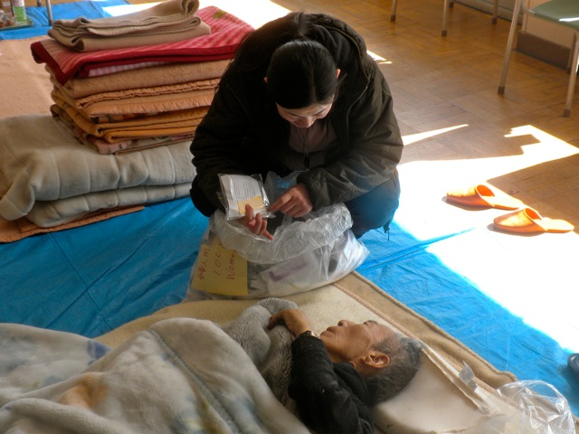 Photo of Rumiko giving socks to a survivor in Iwaki