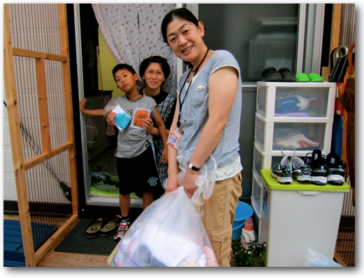 Rumiko distributing socks to a family in their temporary home