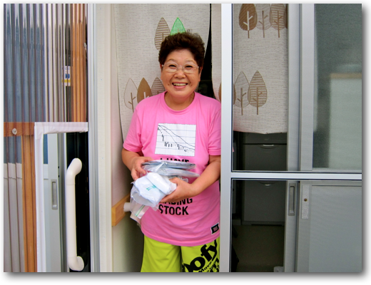 Cheerful grandmother receiving socks in her temporary home